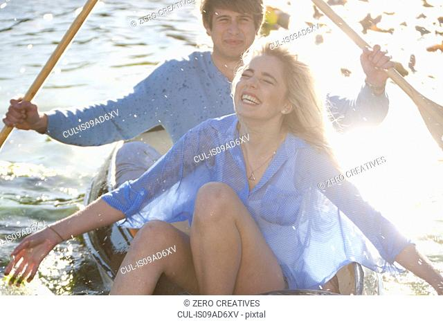 Young romantic couple splashing around in rowing boat