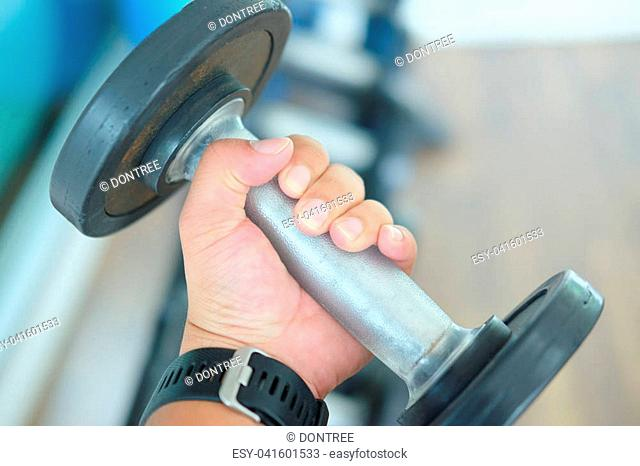 Close up man hand taking iron dumbbells for exercising with it in health club