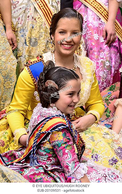 Reina Fallera in traditional Valencian costume taking a break with young child also in traditional Valencian costume during Las Fallas festival