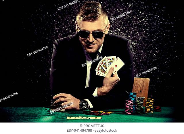 A wealthy mature man drinking brandy and playing poker with the excitement in a casino. Gambling, playing cards and roulette