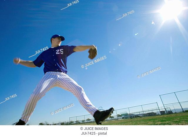 Baseball pitcher, in blue uniform, preparing to throw ball during competitive game, side view lens flare, surface level, tilt