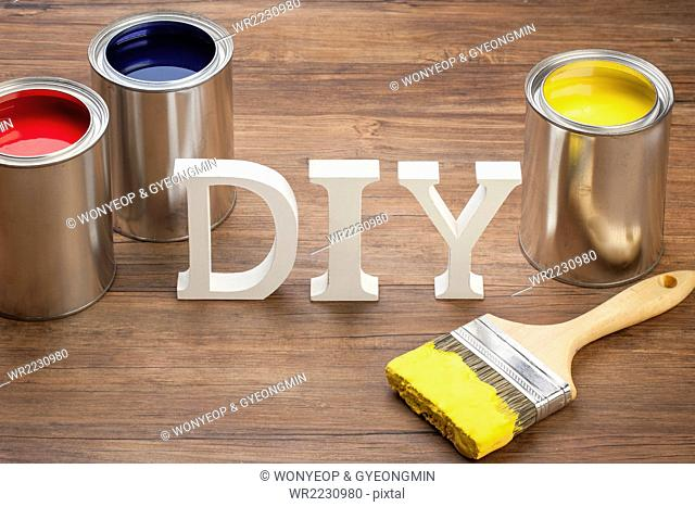 Solid word DIY standing with three different color paint pots with a paint brush coated with yellow paint