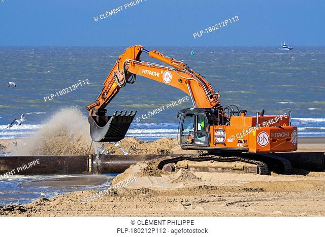 Hydraulic excavator connecting pipes of pipeline during sand replenishment / beach nourishment works along the Belgian coast at Ostend, Belgium