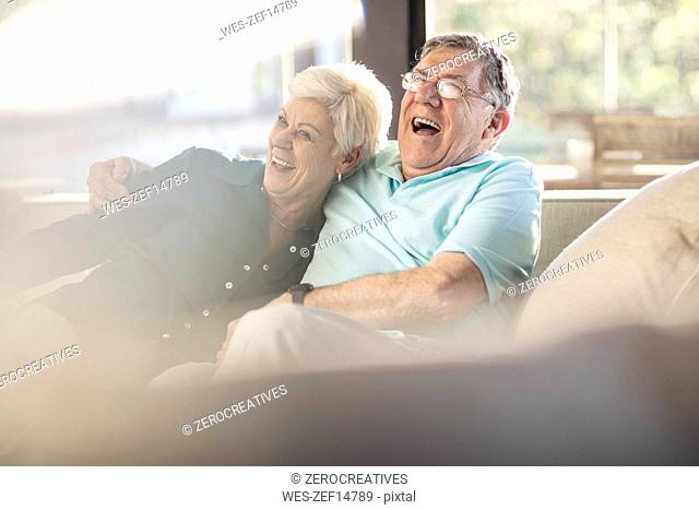 Happy senior couple on couch at home