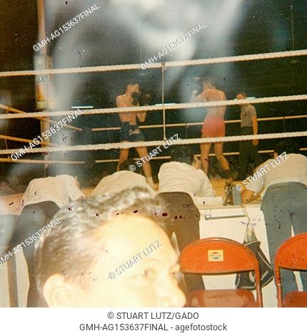 A Vietnamese man smoking a cigarette is caught in a camera's flash, amid a plume of smoke, as American soldiers gather around a boxing ring and watch a boxing...