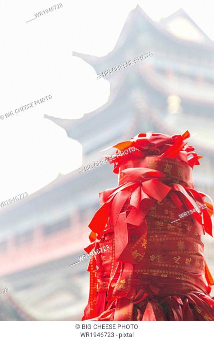Red ribbons tied to a stone post in front of an ancient temple, Chongqing, China