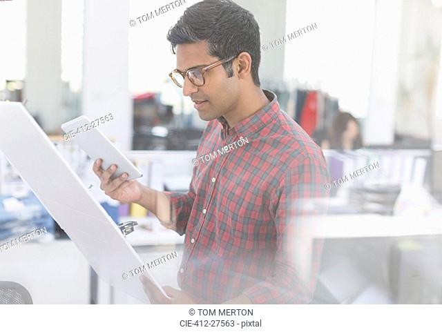 Fashion designer with digital tablet examining story board in office