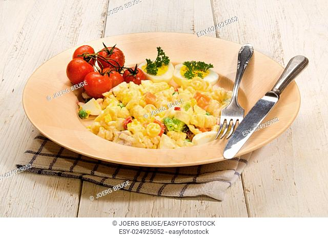 mixed vegetarian pasta salad with egg and vegetables on a wooden plate