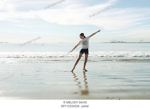 A girl in a dance pose at the beach; Long Beach, California, United States of America