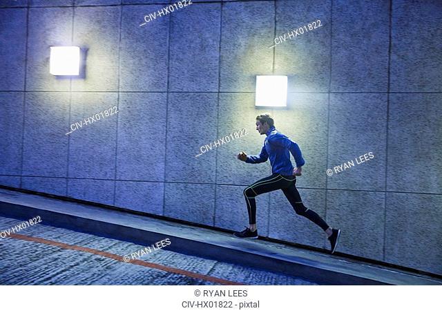 Male runner running ascending illuminated urban ramp