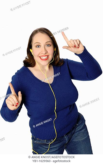 Young lively woman listening to music in an MP3 player and dancing a lively dance