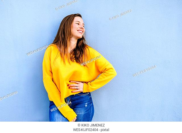 Happy young woman with yellow pullover standing at blue wall