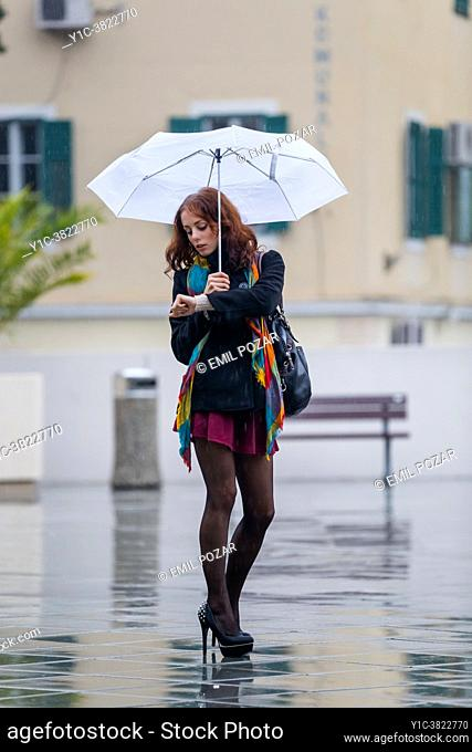 Teen girl on rainy day anxiously and nervously looking at wrist watch