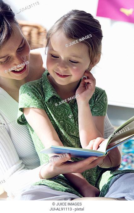 Preschool teacher reading to young girl