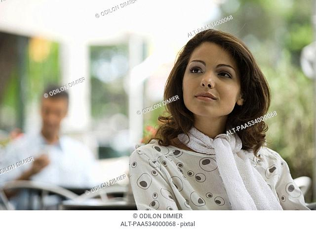 Young woman sitting in sidewalk cafe, smiling