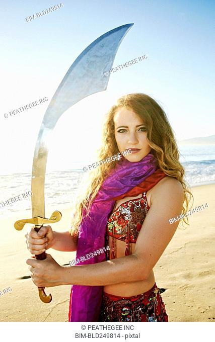 Caucasian belly dancer holding sword on beach