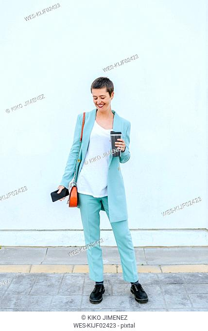 Woman in suit jacket carrying thermo mug and mobile phone