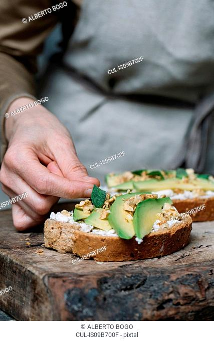 Woman placing herbs on ricotta, avocado and walnut bruschetta, close-up