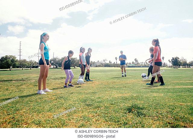 Schoolgirls face to face kicking soccer ball to each other on school sports field