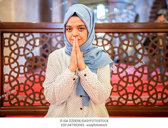 Muslim woman in headscarf and hijab prays while clasping her hands with mosque on background. Religion praying concept