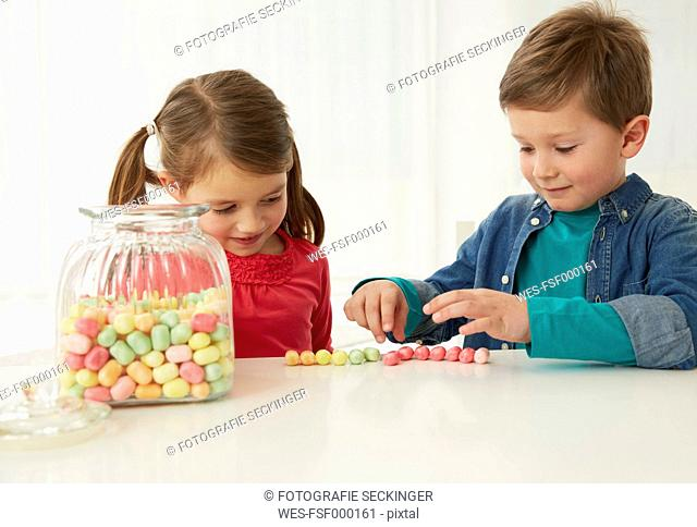 Germany, Munich, Boy and girl with candy jar
