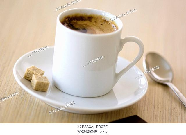 Close-up of a cup of espresso coffee and sugar cubes on a saucer