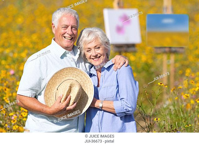 Portrait of smiling senior couple painting in sunny wildflower meadow