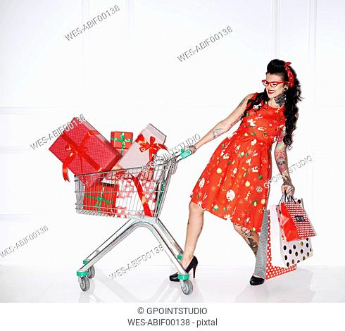 Tattooed woman with shopping bags and shopping cart full of gifts