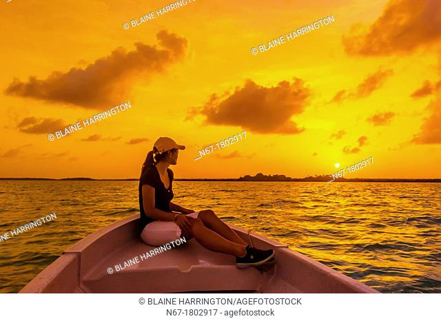 Woman in a ponga boat crossing the Sian Ka'an Biosphere Reserve at sunset, which is a small ecotourism and education center