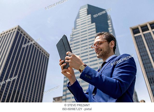 Smiling young businessman looking at digital tablet by New York skyscrapers, USA