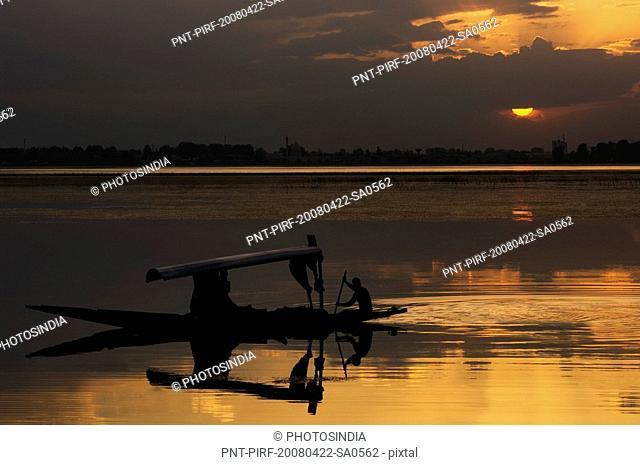 Silhouette of a person rowing a shikara, Dal lake, Srinagar, Jammu and Kashmir, India