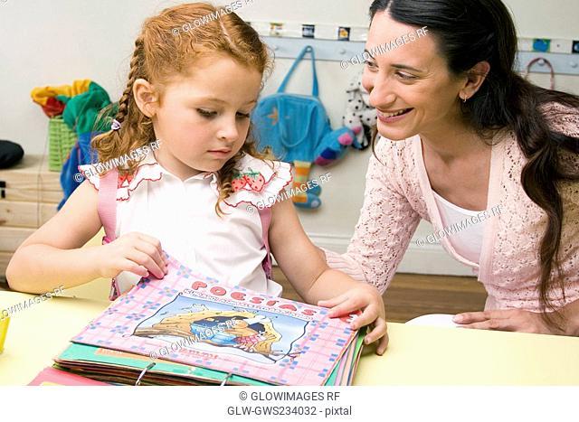 Female teacher teaching her student in a classroom