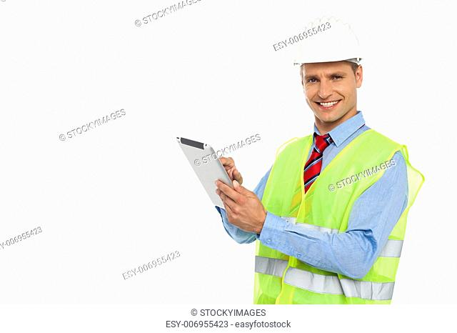 Construction engineer wearing safety hat and operating wireless device