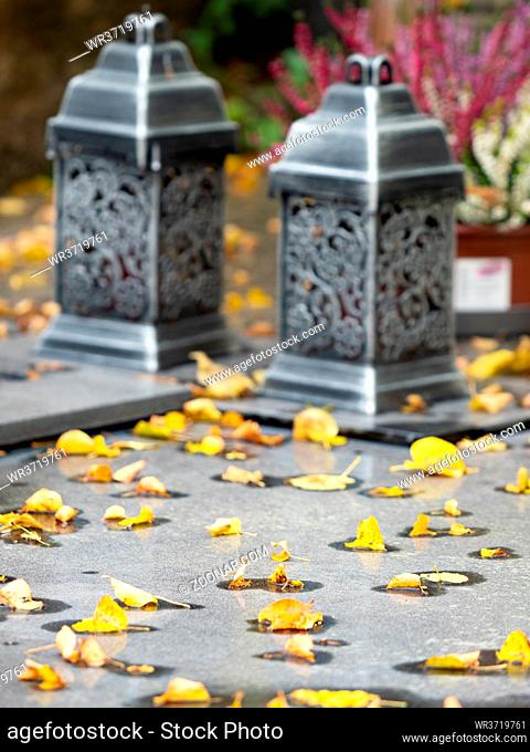 Lanterns on granite tombstone. Old town graveyard in forest park. 24th of October 2020. Hronov, Czechia