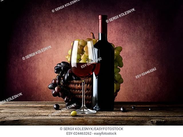 Red wine with basket of grape on table
