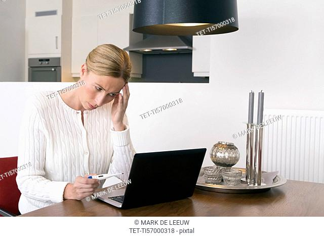 Overworked woman using laptop and holding thermometer