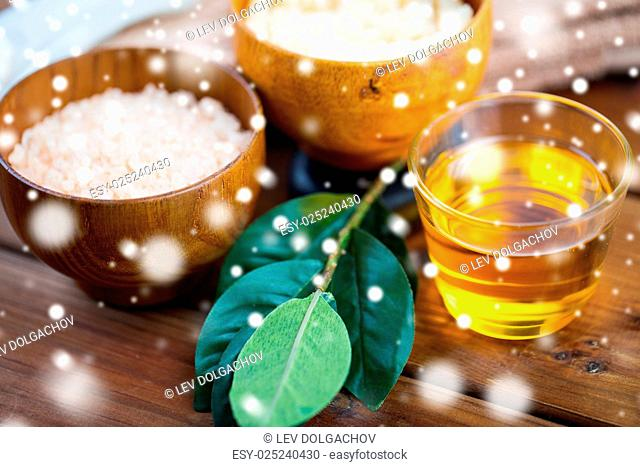 beauty, spa, body care and natural cosmetics concept - honey in glass with himalayan pink salt and leaves on wooden table over snow