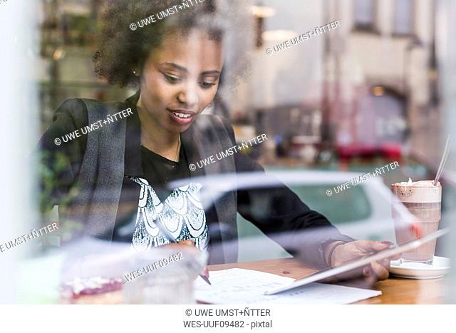 Young woman using tablet in a cafe