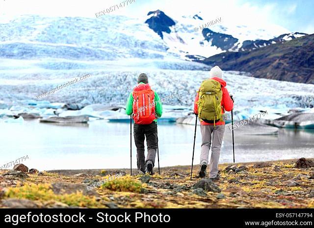 Hikers - people on adventure travel on Iceland. Hiking man man woman walking to glacier and glacial lagoon / lake of Fjallsarlon, Vatna glacier