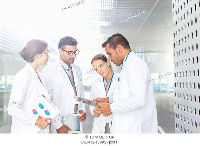 Doctors with clipboard talking in hospital corridor
