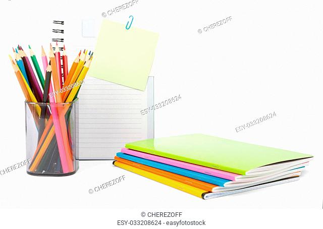 Crayons with notebooks on isolated white background, front view