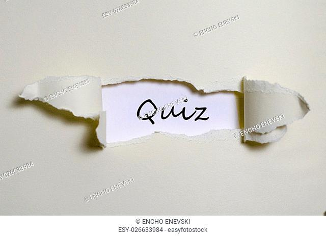 The word quiz appearing behind torn paper
