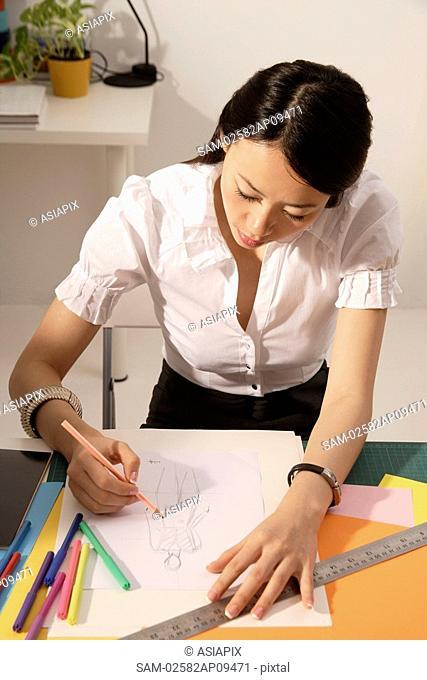 Chinese fashion designer sketching at work desk