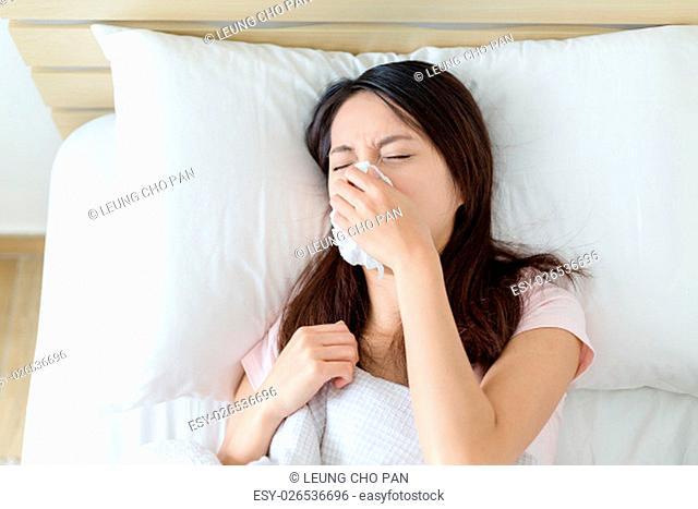 Sick Woman sneezing into Tissue