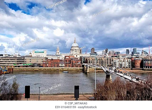 LONDON - March 23: urban landscape with St. Paul's Cathedral and Millennium Bridge, officially known as the London Millennium Footbridge, on March 23