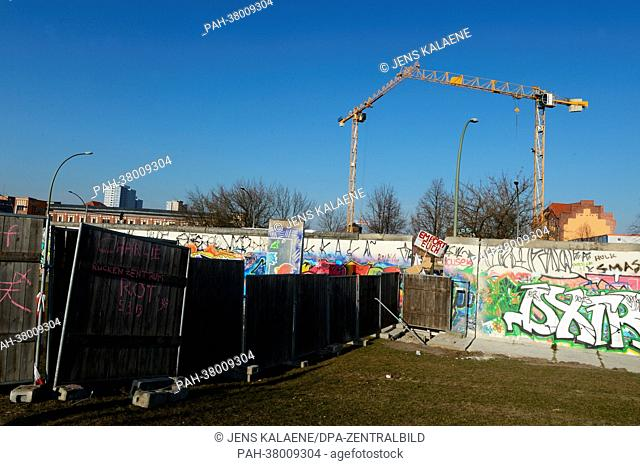 A wooden fence divides the public area from the construction site of luxury apartments (behind the fence) on the west side of the East Side Gallery in Berlin