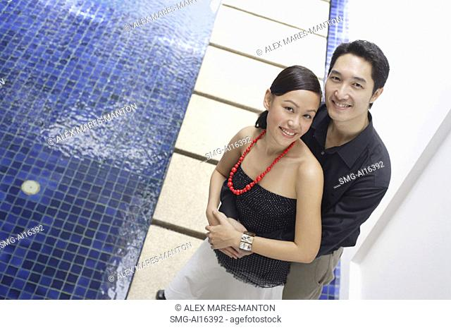 Couple embracing, smiling at camera, high angle view