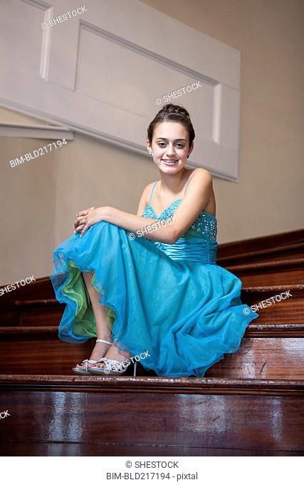 Caucasian teenage girl wearing formal dress on steps