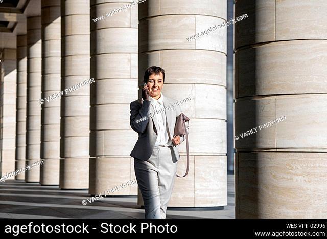 Businesswoman talking on mobile phone while walking against pillar