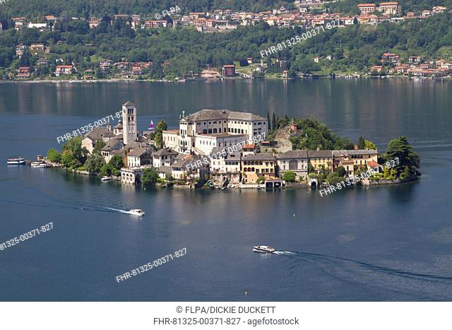 View of lake island and water taxis, Isola San Giulio, Lake Orta, Piedmont, Italy, May
